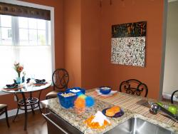 The highlight of this blue and orange kitchen is the Grey Zeien painting on the wall.